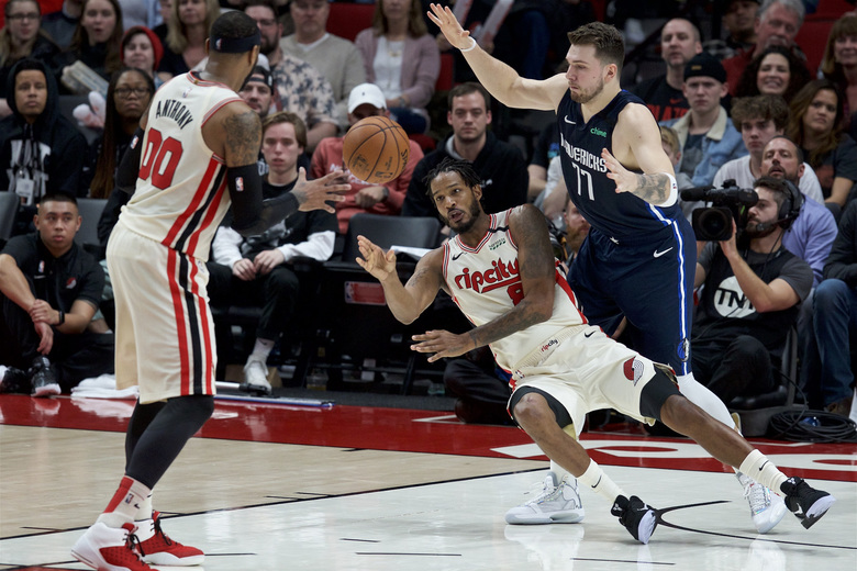 Portland Trail Blazers forward Trevor Ariza, center, passes the ball to forward Carmelo Anthony, left, while Dallas Mavericks guard Luka Doncic defends during the second half of an NBA basketball game in Portland, Ore., Thursday, Jan. 23, 2020. (AP Photo/Craig Mitchelldyer)
