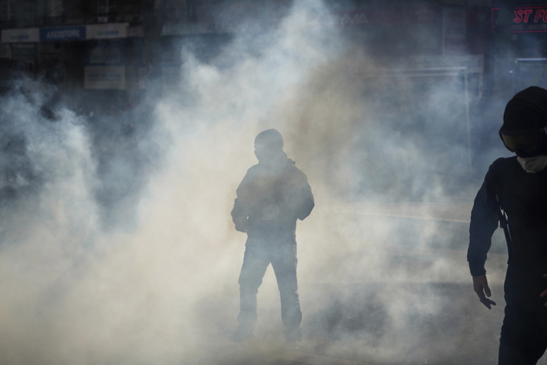 A protester stands in the tear gas during a clash with riot police officers during a demonstration in Lyon, central France, Thursday, Jan. 9, 2020. Rail workers, teachers, doctors, lawyers and others joined a nationwide day of protests and strikes Thursday to denounce French President Emmanuel Macron's plans to overhaul the pension system. Banner reads: Striking until withdrawal. (AP Photo/Laurent Cipriani)