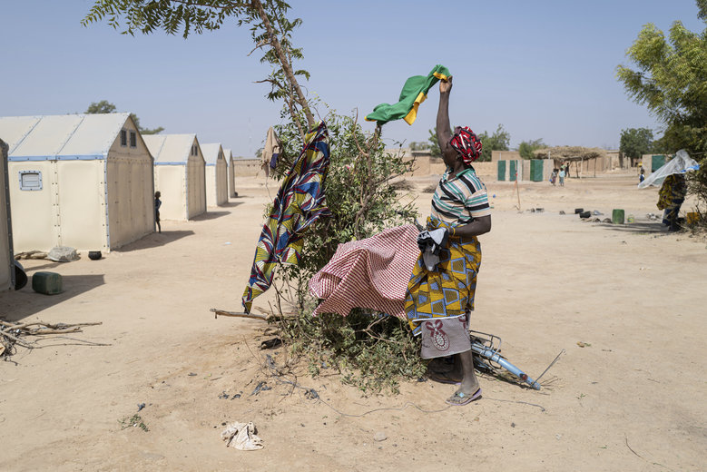 In this photo taken on Tuesday Dec. 10, 2019, a displaced Burkinabe woman picks up her clothes in the Pissila town camp, near Kaya, Burkina Faso. Islamic extremists carried out a record number of attacks last year in Burkina Faso and the instability has now spread to the country's east. The violence in northern and now eastern Burkina Faso has displaced more than half a million people, according to the United Nations. And there are fears the unrest could throw elections planned for late 2020 into question. (AP Photo/Sylvain Cherkaoui)