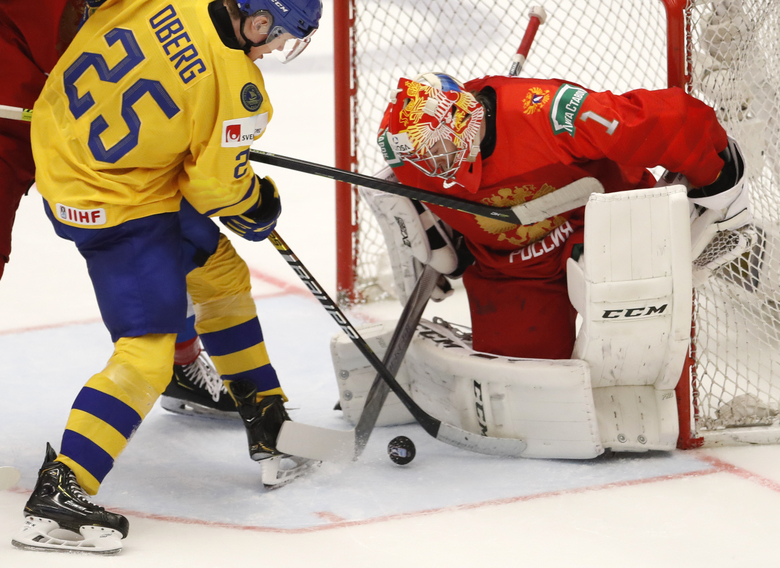 Russia's goaltender Amir Miftakhov, right, makes a save against Sweden's Linus Oberg, left, during the U20 Ice Hockey Worlds semifinal match between Sweden and Russia in Ostrava, Czech Republic, Saturday, Jan. 4, 2020. (AP Photo/Petr David Josek)