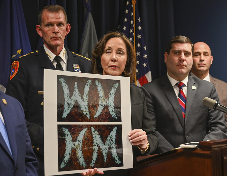 Suffolk County Police Commissioner Geraldine Hart shows a photograph with the initials on a belt, showing either an HM or WH, depending on the angle, during a press conference at police headquarters in Yaphank , N.Y., Thursday, Jan. 16, 2020. Investigators stymied by a nine-year mystery following the discovery of 11 sets of human remains strewn along a suburban New York beach highway revealed a previously unreleased photograph Thursday of evidence found at one of the crime scenes that they say was handled by an unknown suspect. (James Carbone/Newsday via AP)