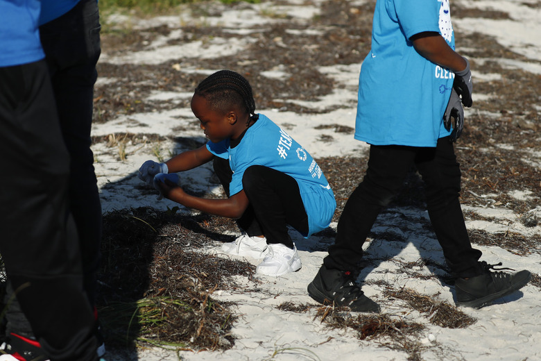 Rasheem Thomas gathers trash on the beach for the Huddle for 100 beach clean up at the Historic Virginia Key Beach Park on Tuesday, Jan. 28, 2020, in Miami. Climate change poses a threat to South Florida's way of life, including Miami's customary spot in the NFL's Super Bowl rotation. The game will be played Sunday in Miami for the 11th time, the most of any city. But the sea and temperature are rising, which could eventually make South Florida an unsuitable Super Bowl site. (AP Photo/Brynn Anderson)