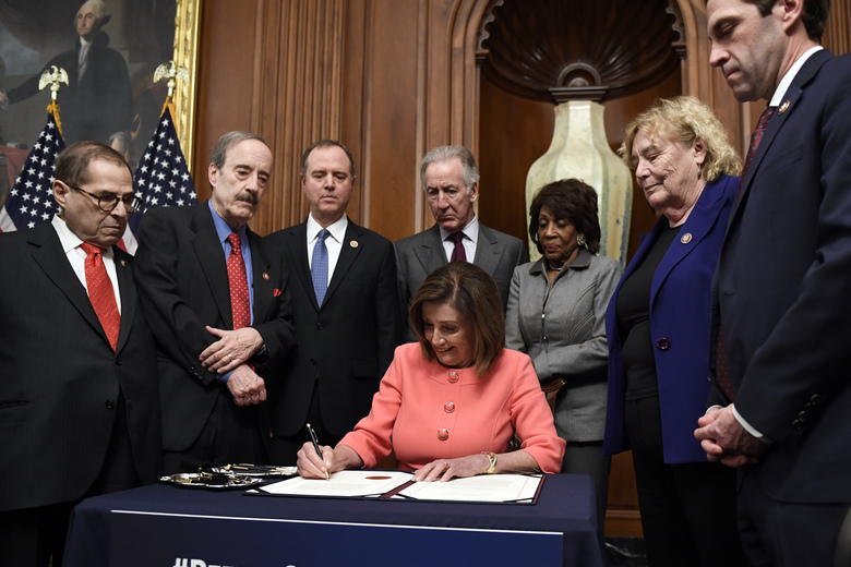 House Speaker Nancy Pelosi of Calif., signs the resolution to transmit the two articles of impeachment against President Donald Trump to the Senate for trial on Capitol Hill in Washington, Wednesday, Jan. 15, 2020. The two articles of impeachment against Trump are for abuse of power and obstruction of Congress. (AP Photo/Susan Walsh)