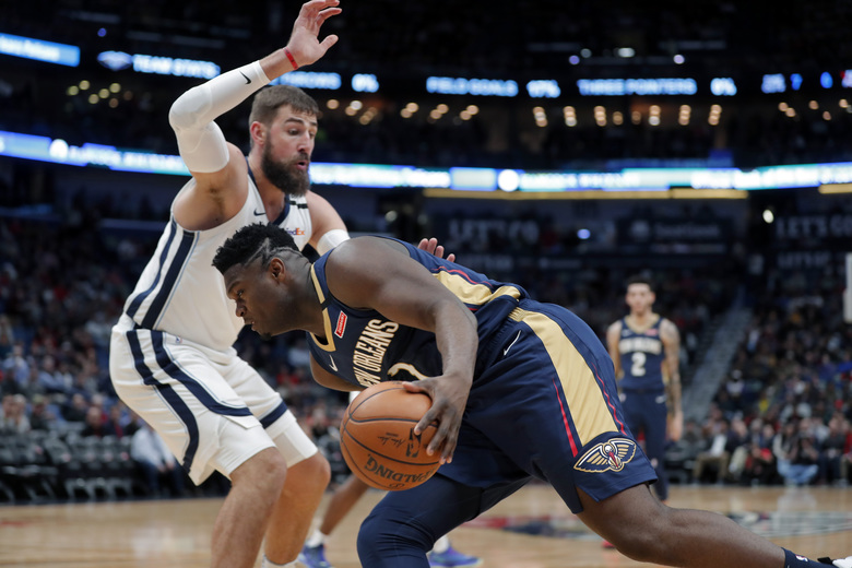 New Orleans Pelicans forward Zion Williamson drives to the basket against Memphis Grizzlies center Jonas Valanciunas during the first half of an NBA basketball game in New Orleans, Friday, Jan. 31, 2020. (AP Photo/Gerald Herbert)