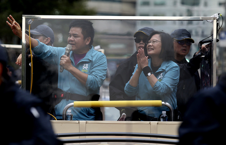 Taiwan's President Tsai Ing-wen, center, also presidential election candidate for the Democratic Progressive Party (DPP), waves to the crowd from an election campaign car in Taipei, Taiwan, Friday, Jan. 10, 2020. Taiwan will hold its presidential election on Jan. 11. (AP Photo/Chiang Ying-ying)
