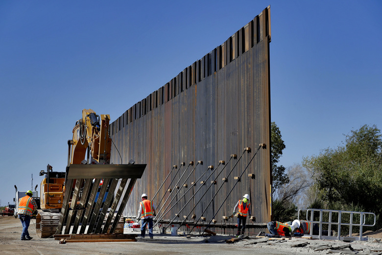 FILE – In this Sept. 10, 2019 file photo, government contractors erect a section of Pentagon-funded border wall along the Colorado River in Yuma, Ariz. The White House says construction of the U.S.-Mexico border wall will move forward after a federal appeals court ruling that frees up construction money. The 2-1 ruling on Wednesday halted a federal judge's ruling in December that had prevented the government from spending $3.6 billion diverted from 127 military construction projects to pay for 175 miles of border wall.  (AP Photo/Matt York)
