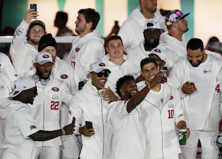 San Francisco 49ers take selfies as they arrive for Opening Night for the NFL Super Bowl 54 football game Monday, Jan. 27, 2020, at Marlins Park in Miami. (AP Photo/Morry Gash)