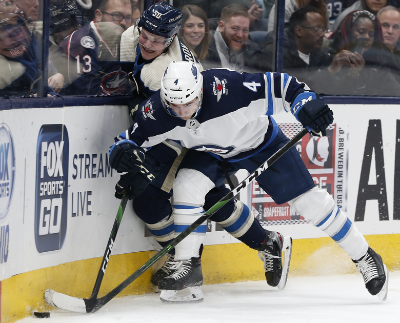 Winnipeg Jets' Neal Pionk, right, checks Columbus Blue Jackets' Eric Robinson during the second period of an NHL hockey game Wednesday, Jan. 22, 2020, in Columbus, Ohio. (AP Photo/Jay LaPrete)