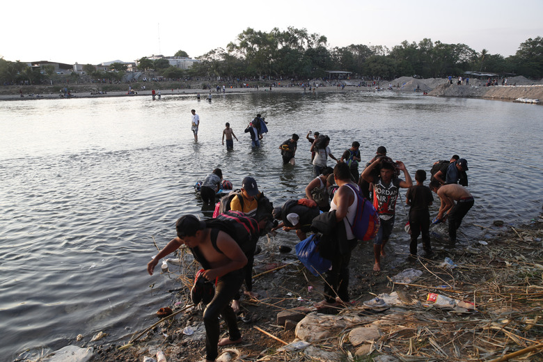 Central American migrants return to the Guatemala shore of the Suchiate river on the border with Mexico, in Tecun Uman, Guatemala, Monday, Jan. 20, 2020. The migrants remained at the river's edge or stood in its muddy waters trying to decide what to do next, after being blocked from crossing en masse across the river. (AP Photo/Moises Castillo)