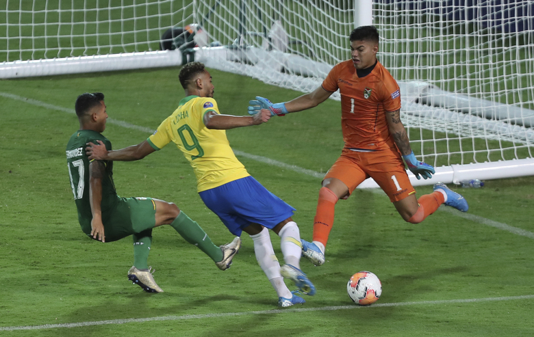 Brazil's Matheus Cunha, center, strikes the ball in an attempt to score against Bolivia during a South America Olympic qualifying U23 soccer match at Centenario stadium in Armenia, Colombia, Tuesday, Jan. 28, 2020. (AP Photo/Fernando Vergara)