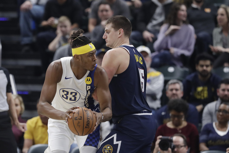 Indiana Pacers' Myles Turner (33) goes to the basket against Denver Nuggets' Nikola Jokic (15) during the first half of an NBA basketball game Thursday, Jan. 2, 2020, in Indianapolis. (AP Photo/Darron Cummings)