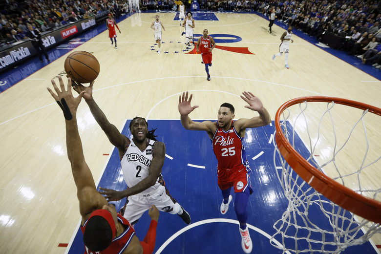 Brooklyn Nets' Taurean Prince, center, goes up for a shot between Philadelphia 76ers' Tobias Harris, left, and Ben Simmons during the first half of an NBA basketball game, Wednesday, Jan. 15, 2020, in Philadelphia. (AP Photo/Matt Slocum)