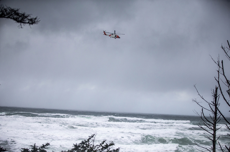 A Coast Guard helicopter searches on Sunday for a missing boy near Falcon Cove Beach in Clastop County, Ore. (Mark Graves / The Oregonian via AP)