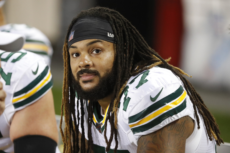"""FILE – In this Thursday, Sept. 5, 2019 file photo, Green Bay Packers offensive tackle Billy Turner sits on the bench during an NFL football game against the Chicago Bears in Chicago. Green Bay Packers right guard William """"Billy"""" Turner's perspective on life was bleak and negative after he was cut by the Dolphins in October 2016. But more than three years later, Turner's outlook has changed, and the 6-foot-5, 310-pound guard's conscious mission to spread positive energy has become a driving force behind the Packers' success this season.(AP Photo/Charles Rex Arbogast, File)"""