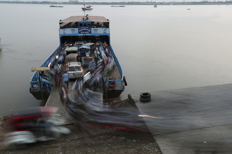 Passengers get off from a ferry after crossing the Mekong river from Arey Ksat to Phnom Penh, Cambodia, Tuesday, Jan. 21, 2020. (AP Photo/Heng Sinith)