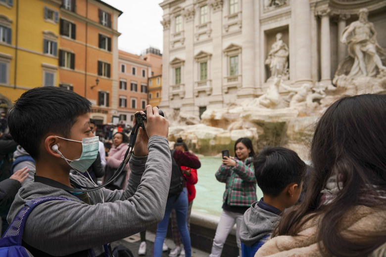 A tourist from China wears a mask as he takes photos of the Trevi Fountain, in Rome, Friday, Jan. 31, 2020. Italy banned all flights coming from and going to China as European countries have stepped up their response to the new virus that has sickened thousands of people in China and reached 19 other countries. (AP Photo/Andrew Medichini)