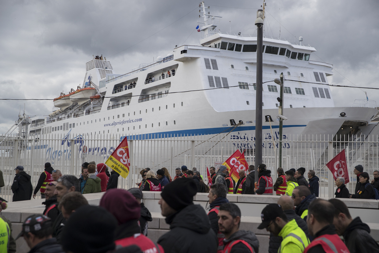 Strikers march past a ferry held at the Marseille port during a demonstration Tuesday, Jan. 14, 2020, in Marseille, southern France. Rail workers, teachers, doctors, lawyers and others joined another nationwide day of protests and strikes Tuesday to denounce French President Emmanuel Macron's plans to overhaul the pension system. (AP Photo/Daniel Cole)