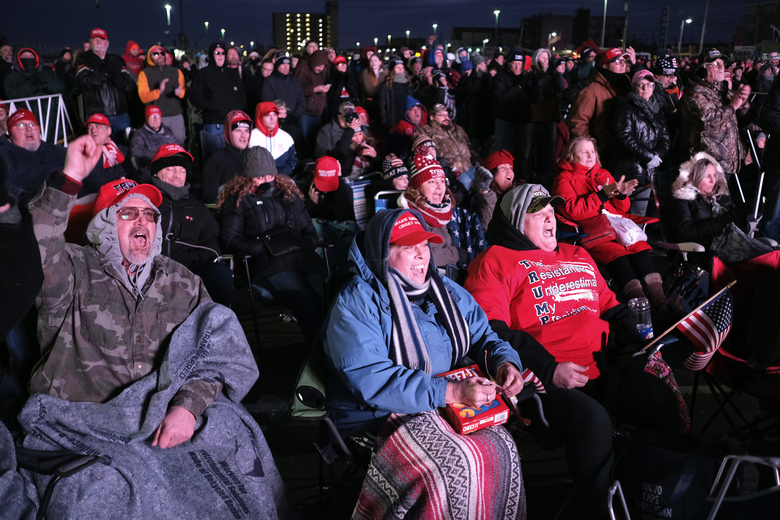 People watch a President Donald Trump campaign rally on a large screen television in parking lot outside the convention center in Wildwood, N.J., Tuesday, Jan. 28, 2020. (AP Photo/Seth Wenig)