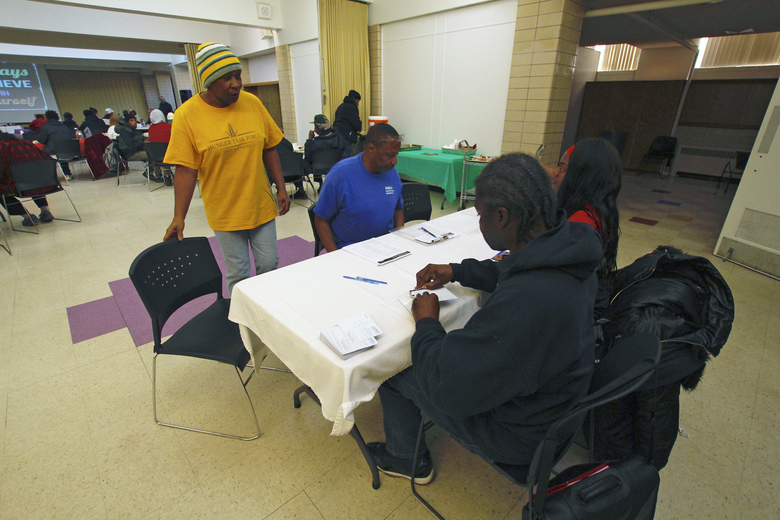In this Dec. 11, 2019, photo, Sheila McDonald, left, stops at a table with Travis Taylor and Roniqua White at Our Savior's Lutheran Church during a free lunch, in Milwaukee. Taylor and White are helping Ex-Prisoners Organizing, or EXPO, a statewide group of former prisoners, educate people about their rights and get them to turn out to vote in 2020. (AP Photo/Carrie Antlfinger)