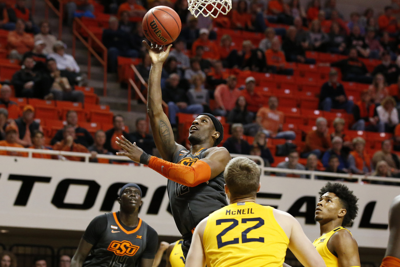 Oklahoma State forward Cameron McGriff, top, shoots in front of West Virginia guard Sean McNeil (22) in the first half of an NCAA college basketball game in Stillwater, Okla., Monday, Jan. 6, 2020. (AP Photo/Sue Ogrocki)