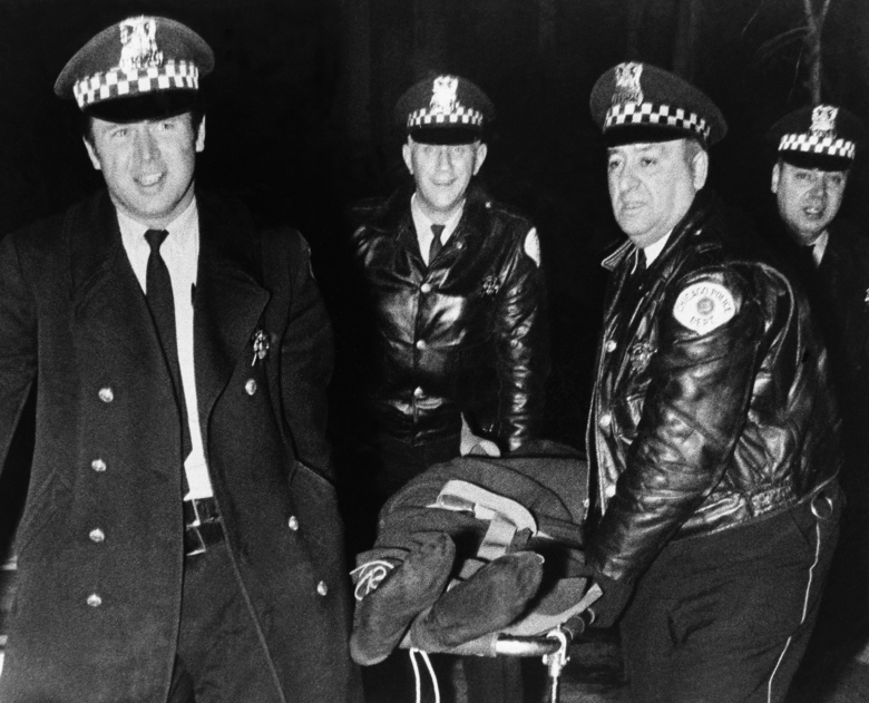 """FILE – In this Dec. 4, 1969, file photo, Chicago police remove the body of Fred Hampton, leader of the Illinois Black Panther Party, who was slain in a gun battle with police in Chicago. """"The First Rainbow Coalition,"""" a new PBS documentary, is exploring a little-known movement in 1960s Chicago that brought together blacks, Latinos, and poor whites from Appalachia to fight police brutality. (AP Photo/File)"""