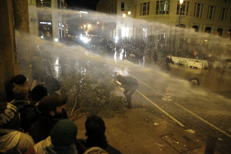 Anti-government protesters are sprayed by a water cannon as they clash with the riot police during ongoing protests in Beirut, Lebanon, Wednesday, Jan. 22, 2020. Lebanon's new government held its first meeting Wednesday, a day after it was formed following a three-month political vacuum, with the prime minister saying his Cabinet will adopt financial and economic methods different than those of previous governments. (AP Photo/Bilal Hussein)