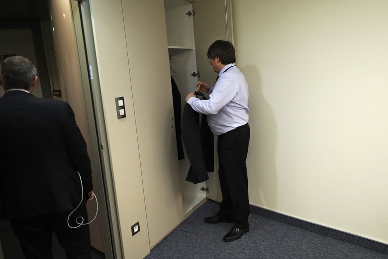 Catalonia's former regional president Carles Puigdemont hangs his jacket in his bare new office at the European Parliament in Strasbourg, eastern France, Monday, Jan. 13, 2020. Puigdemont attended his first session as a member of the European Parliament despite facing an arrest warrant against him in Spain. (AP Photo/Francisco Seco)