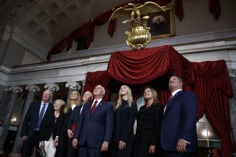 The family of Sen. Kelly Loeffler, R-Ga., third from left, looks up at a photographer in the balcony, Monday Jan. 6, 2020, with Vice President Mike Pence, center, after a re-enactment of her swearing-on Capitol Hill in Washington. From left are Loeffler's parents Don Loeffler and Lynda Loeffler, Loeffler, her husband Jeffrey Sprecher, neice Addison Loeffler, Molly Loeffler, and Brian Loeffler. (AP Photo/Jacquelyn Martin)