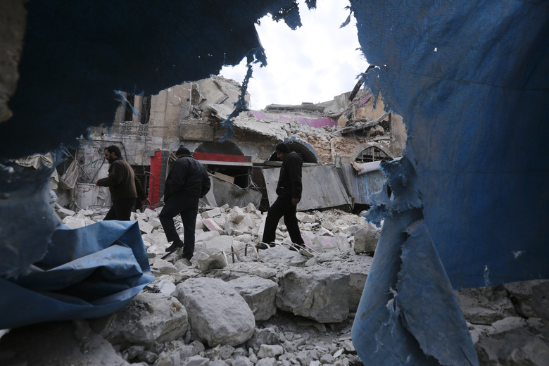 People walk past destruction by the government airstrikes in the town of Ariha, in Idlib province, Syria, Wednesday, Jan. 15, 2020. Syrian government warplanes struck a market and an industrial area Wednesday in the last territory in the hands of rebel groups in the country's northwest, killing at least 15 people, opposition activists said. (AP Photo/Ghaith Alsayed)