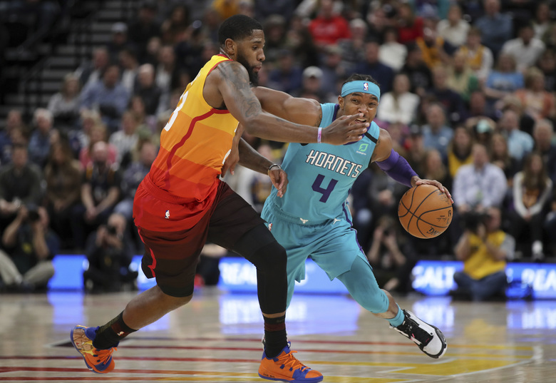 Charlotte Hornets guard Devonte' Graham (4) tries to dribble around Utah Jazz forward Royce O'Neale (23) and up the court during the second quarter of an NBA basketball game Friday, Jan. 10, 2020, in Salt Lake City. (AP Photo/Chris Nicoll)