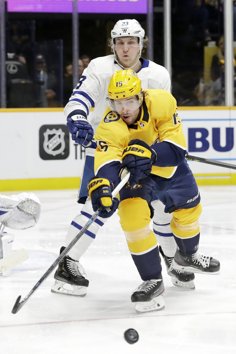 Nashville Predators right wing Craig Smith (15) reaches for the puck in front of Toronto Maple Leafs defenseman Travis Dermott (23) in the second period of an NHL hockey game Monday, Jan. 27, 2020, in Nashville, Tenn. (AP Photo/Mark Humphrey)