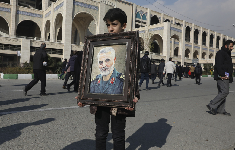 "A boy carries a portrait of Iranian Revolutionary Guard Gen. Qassem Soleimani, who was killed in the U.S. airstrike in Iraq, prior to the Friday prayers in Tehran, Iran. Iran has vowed ""harsh retaliation"" for the U.S. airstrike near Baghdad's airport that killed Tehran's top general and the architect of its interventions across the Middle East, as tensions soared in the wake of the targeted killing. (AP Photo/Vahid Salemi)"