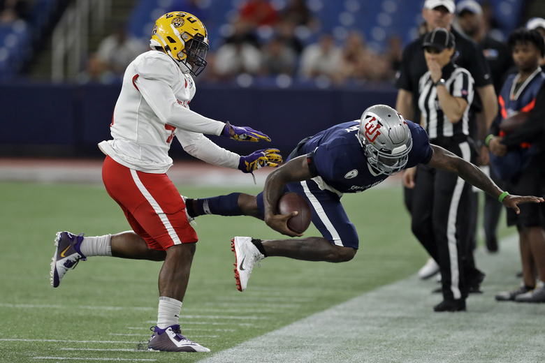 East linebacker Michael Divinity Jr., of LSU, (45) shoves West quarterback Tyler Huntley, of Utah, (1) out of bounds after a run during the second half of the East West Shrine football game Saturday, Jan. 18, 2020, in St. Petersburg, Fla. (AP Photo/Chris O'Meara)