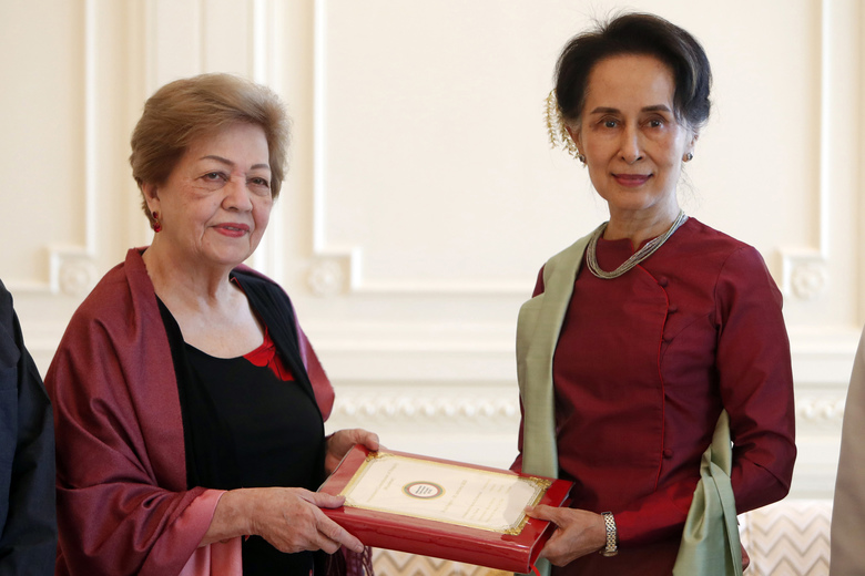 FILE – In this Jan. 20, 2020, file photo, Myanmar's leader Aung San Suu Kyi, right, receives a final report from Philippine diplomat Rosario Manalo, a member of the Independent Commission of Enquiry for Rakhine State, at the Presidential Palace in Naypyitaw, Myanmar. When Suu Kyi walked into the International Court of Justice in December, 2019, she gambled the remaining shreds of her hard-won international reputation on a rebuttal of accusations that her country's military committed genocide against minority Rohingya Muslims. (AP Photo/Aung Shine Oo, File)