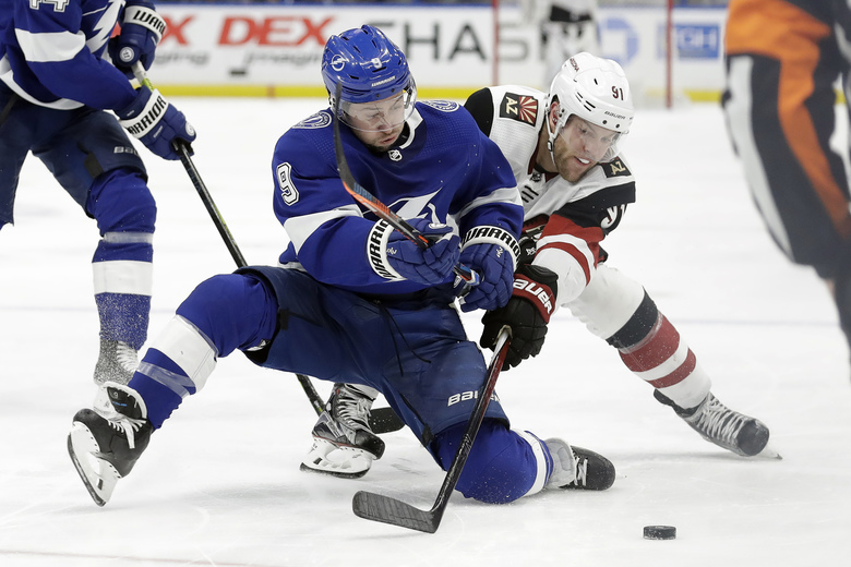 Tampa Bay Lightning center Tyler Johnson (9) and Arizona Coyotes left wing Taylor Hall (91) vie for the puck during the third period of an NHL hockey game Thursday, Jan. 9, 2020, in Tampa, Fla. (AP Photo/Chris O'Meara)
