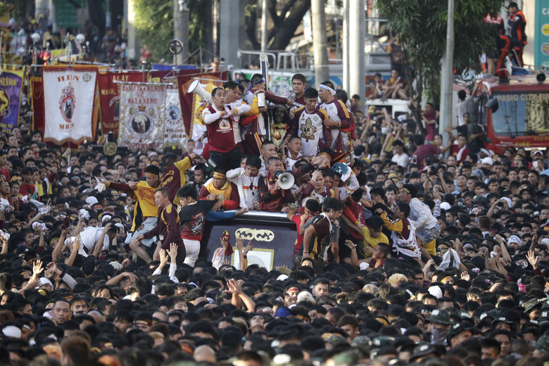 Devotees try to climb the carriage of the Black Nazarene during a raucous procession to celebrate its feast day Thursday, Jan. 9, 2020, in Manila, Philippines. A mammoth crowd of mostly barefoot Filipino Catholics prayed for peace in the increasingly volatile Middle East at the start Thursday of an annual procession of a centuries-old black statue of Jesus Christ in one of Asia's biggest religious events. (AP Photo/Aaron Favila)