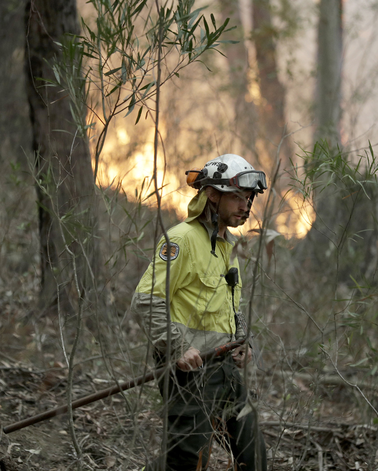 A firefighter keeps an eye on a controlled burn used to control a larger fire near Burrill Lake, Australia, Sunday, Jan. 5, 2020. Milder temperatures Sunday brought hope of a respite from wildfires that have ravaged three Australian states, destroying almost 2,000 homes. (AP Photo/Rick Rycroft)