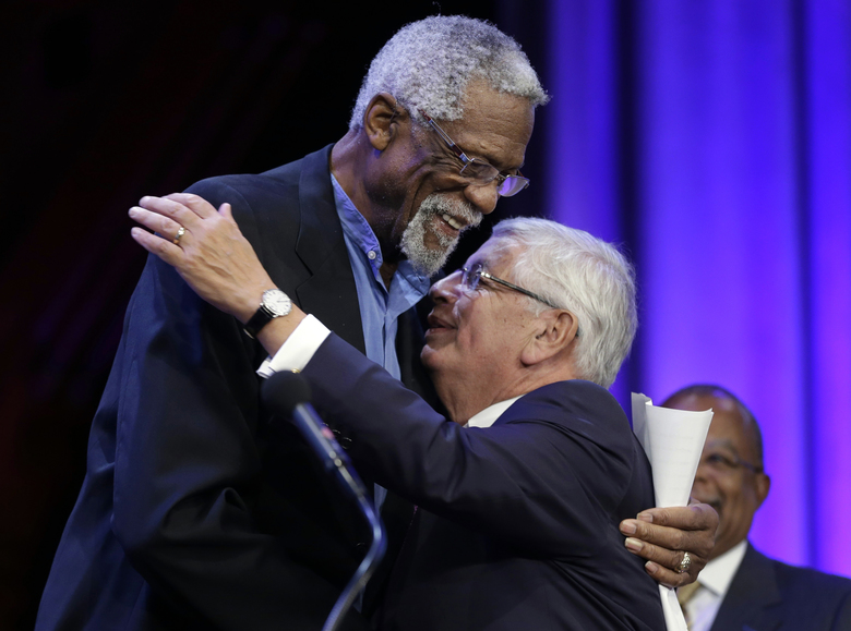 FILE – In this Wednesday, Oct. 2, 2013 file photo, Former Boston Celtics basketball player Bill Russell, left, hugs National Basketball Association Commissioner David Stern during an award ceremony for the W.E.B. Du Bois Medal at Harvard University, in Cambridge, Mass. David Stern, who spent 30 years as the NBA's longest-serving commissioner and oversaw its growth into a global power, has died on New Year's Day, Wednesday, Jan. 1, 2020. He was 77.  (AP Photo/Steven Senne, FGile)