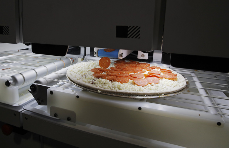 Picnic's pizza-making robot makes a pizza at a food vendor's booth during the CES tech show, Wednesday, Jan. 8, 2020, in Las Vegas. (AP Photo/John Locher)