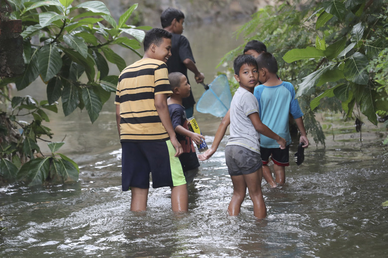 Children look for fish after flooded in Jakarta, Indonesia, Sunday, Jan. 5, 2020. Landslides and floods triggered by torrential downpours have left  dozens of people dead in and around Indonesia's capital, as rescuers struggled to search for people apparently buried under tons of mud, officials said Saturday. (AP Photo/Tatan Syuflana)