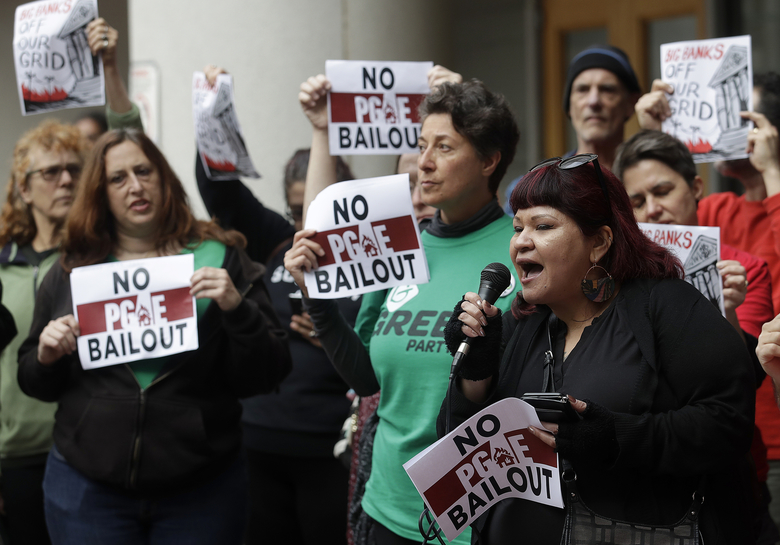 FILE – In this Jan. 28, 2019, file photo, Jessica Tovar, right, speaks at a rally before a California Public Utilities Commission meeting in San Francisco. A state lawmaker is demanding an extensive review of the California Public Utilities Commission to determine whether regulators' lax oversight enabled the neglectful behavior at Pacific Gas & Electric that triggered catastrophic wildfires, a messy bankruptcy and exasperating blackouts. (AP Photo/Jeff Chiu, File)