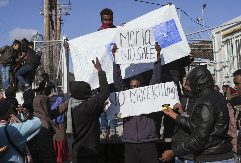 Refugees and migrants hold placards as they demonstate outside Moria camp, following the stabbing death of an 20-year-old man from Yemen in the Greek island of Lesbos, Friday, Jan, 17, 2020. Authorities arrested a 27-year-old Afghan migrant in connection with the incident. Overcrowding at Moria has steadily worsened over the past year as the number of arrivals of migrants and refugees using clandestine routes from Turkey to the Greek islands remains high _ and totaled nearly 60,000 in 2019. (AP Photo/Aggelos Barai)