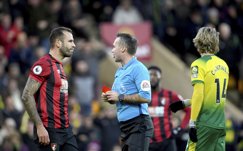 Bournemouth's Steve Cook, left, is sent-off by match referee Paul Tierney during the English Premier League soccer match between Norwich City and Bournemouth at the Carrow Road Stadium, Norwich, England. Saturday, Jan. 18, 2020.(Joe Giddens/PA via AP)