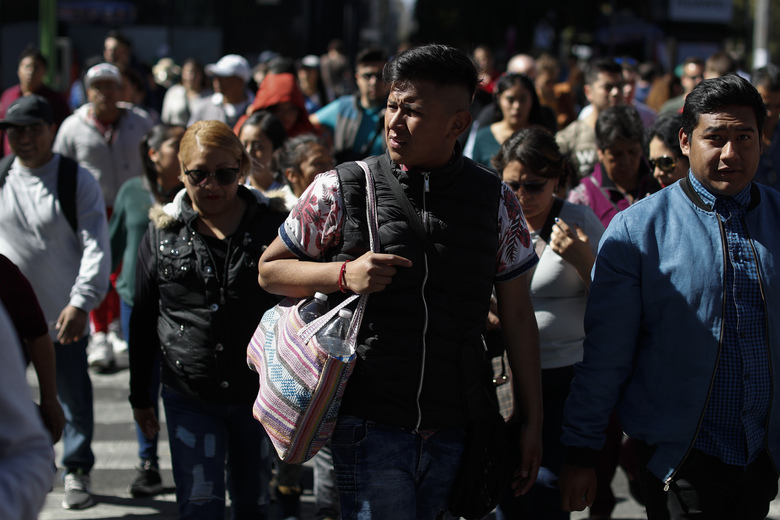 A man carries items in a cloth shopping bag, as he walks in central Mexico City, Wednesday, Jan. 1, 2020. Shoppers in Mexico's massive capital city could be seen Wednesday carrying reusable shopping bags and repurposed used plastic bags, as stores stopped providing disposable plastic bags to their customers in compliance with a city law that took effect with the new year.(AP Photo/Rebecca Blackwell)