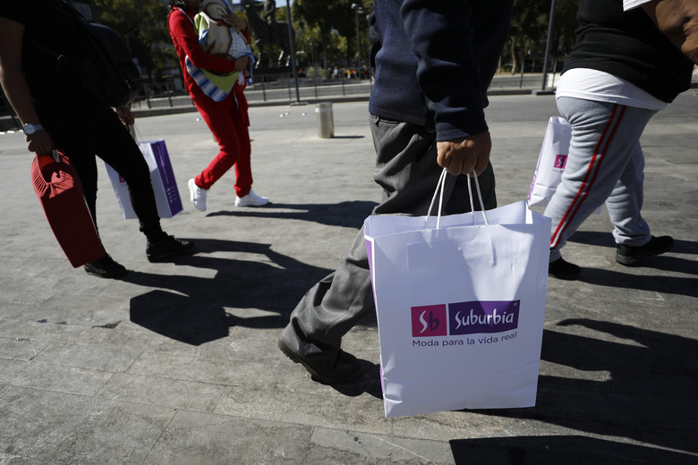 Shoppers carry purchases in paper and cloth bags as they walk in central Mexico City, Wednesday, Jan. 1, 2020. Pedestrians in Mexico's massive capital city could be seen Wednesday carrying reusable shopping bags and repurposed used plastic bags, as stores stopped providing disposable plastic bags to their customers in compliance with a city law that took effect with the new year.(AP Photo/Rebecca Blackwell)