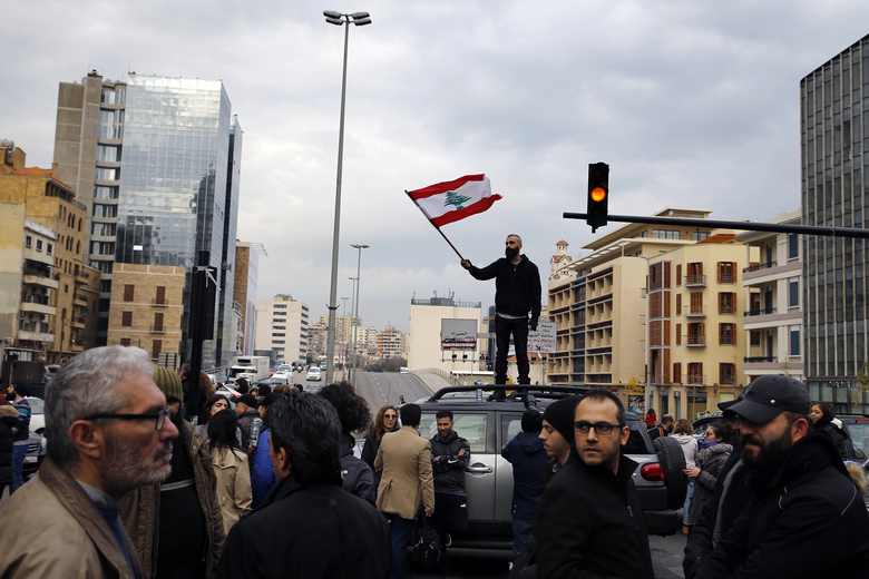 An anti-government protester stands atop his car and waves a national flag as others block a main highway in Beirut, Lebanon, Friday, Jan. 17, 2020. Protesters closed major roads in the capital Beirut and around wide parts of Lebanon paralyzing the country as the political crisis over the formation of a new government worsens. (AP Photo/Bilal Hussein)