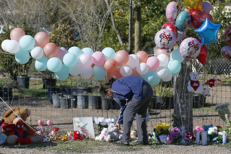 A woman places a stuffed animal at a makeshift memorial Thursday, Jan. 23, 2020, in front of the home where Rachel Henry was arrested on suspicion of killing her three children after they were found dead inside the family home earlier in the week, in Phoenix. (AP Photo/Ross D. Franklin)