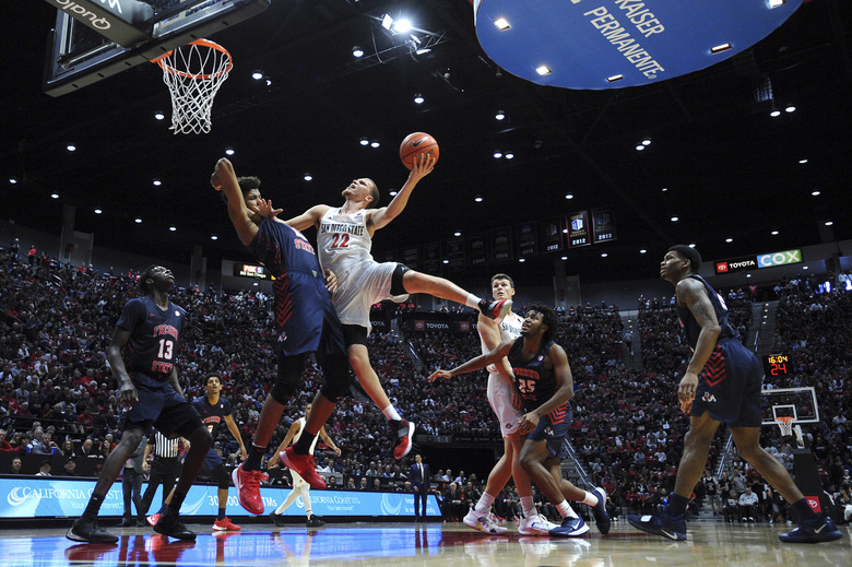 San Diego State guard Malachi Flynn (22) goes to the basket while defended by Fresno State forward Orlando Robinson (10) during the second half of an NCAA college basketball game Wednesday, Jan. 1, 2020, in San Diego. San Diego won 61-52. (AP Photo/Orlando Ramirez)