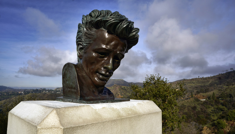 """In this Friday, Jan. 17, 2020, photo, the Hollywood hills are seen behind a bust of actor James Dean at the Griffith Observatory in Los Angeles. Travis Cloyd, who is leading the revival of Dean for his appearance in """"Finding Jack,"""" says his company will eventually offer the late actor's digital likeness for a range of roles in movies, TV and video games. (AP Photo/Richard Vogel)"""