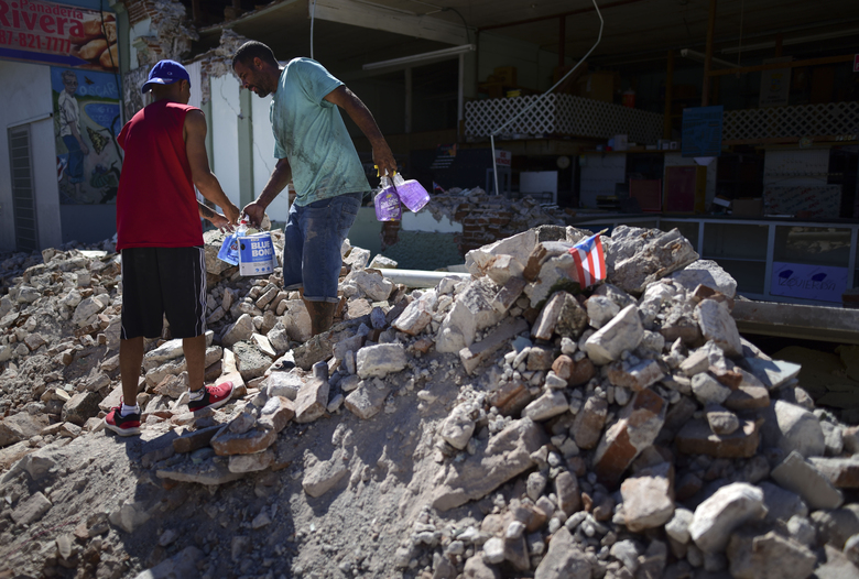 Store owners and family help remove supplies from Ely Mer Mar hardware store, which partially collapsed after an earthquake struck Guanica, Puerto Rico, Tuesday, Jan. 7, 2020. A 6.4-magnitude earthquake struck Puerto Rico before dawn on Tuesday, killing one man, injuring others and collapsing buildings in the southern part of the island. (AP Photo/Carlos Giusti)